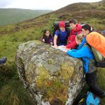 DofE - expedition team with map spread over rock looking at route, Peak District