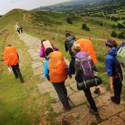 DofE - group on Mam Tor ridge walking away from camera with bright rucksack covers